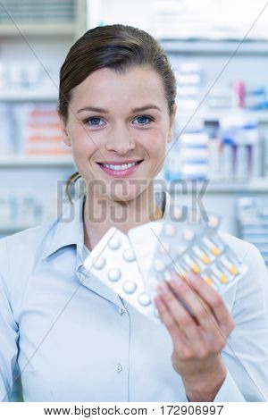 Portrait of pharmacist showing medicine in pharmacy