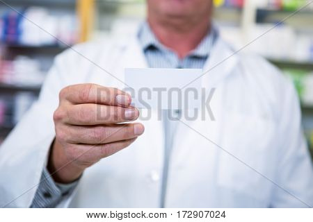 Pharmacist holding a prescription in pharmacy