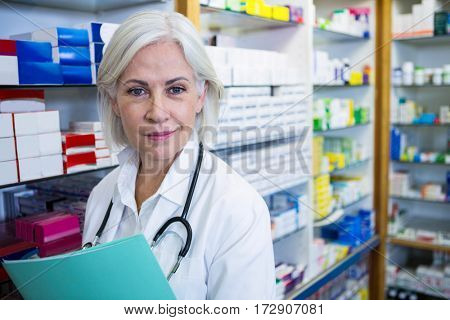 Portrait of pharmacist holding a file in pharmacy