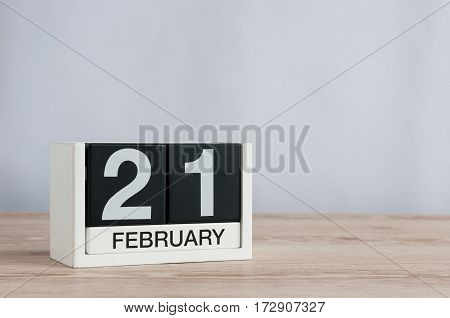 February 21st. Day 21 of month, calendar on wooden background. Winter time. Empty space for text.