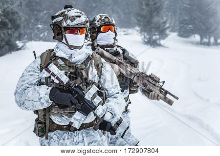 Winter arctic mountains warfare. Action in cold conditions. Troopers with weapons in forest somewhere above the Arctic Circle