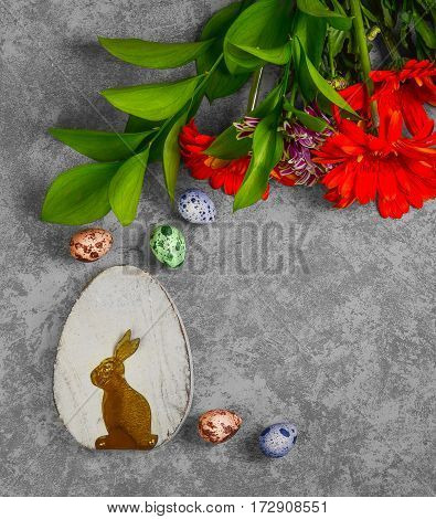 Easter card. On gray concrete background Two wooden eggs with the Easter bunny quail eggs. Easter bouquet of chrysanthemum. Top view from above and copy space.