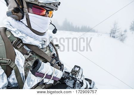 Winter arctic mountains warfare. Action in cold conditions. Trooper with weapons in forest somewhere above the Arctic Circle