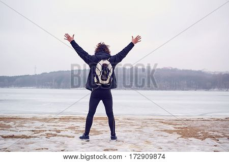 The concept of lifestile travel, adventure, freedom. A man with  backpack put his hands up in  frozen lake winter.