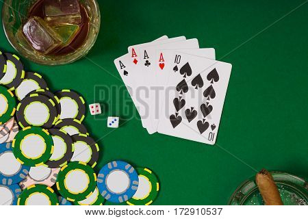 gambling, fortune and entertainment concept - close up of casino chips, whisky glass, playing cards and cigar on green table surface. Top view. Still life