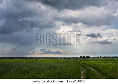 Rural road in green field with blue cloudy sky background landscape