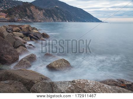 Winter evening view of the sea rocks of Camogli, along the shores of Ligurian Sea (Northern Italy), near the breakwater of the own bay.