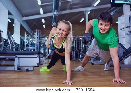 Man and woman doing pushups with dumbbells in his hands on the floor  gym.