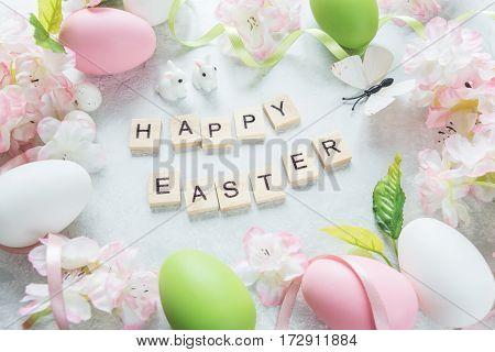 Beautiful delicate Easter composition with pink cherry flowers multicolored Easter eggs Easter bunny butterfly and inscription