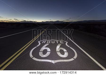 Route 66 pavement sign at night in the Southern California Mojave desert.
