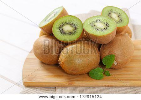 pile of ripe kiwi on wooden cutting board - close up