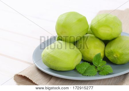 plate of peeled kiwi on beige place mat - close up