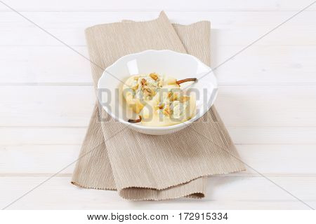 bowl of halved pears with blue cheese and walnuts on beige place mat