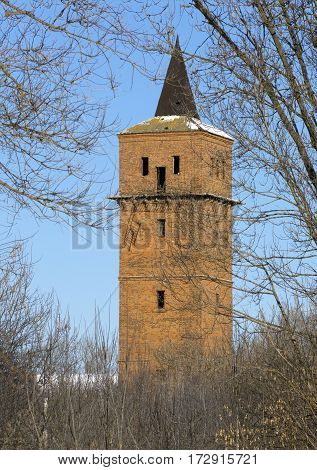old abandoned brick terracotta water lookout tower structure red with a metal spike on the background of blue sky among the trees without foliage winter Russia