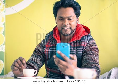 Young indian man messaging with phone and stirring coffee sitting at bar cafe - Handsome bangladeshi happy guy holding mobile on green background - Social media addiction concept