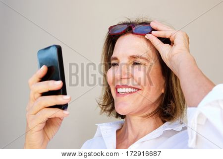 Business Woman Holding Glasses And Looking At Mobile Phone