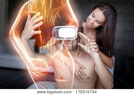 Young man playing virtual reality with headset and girlfriend and virtual girl foreplay in threesome