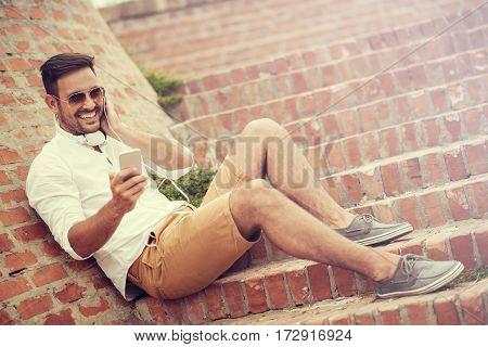 Happy young handsome man with headphones smiling and listening to music