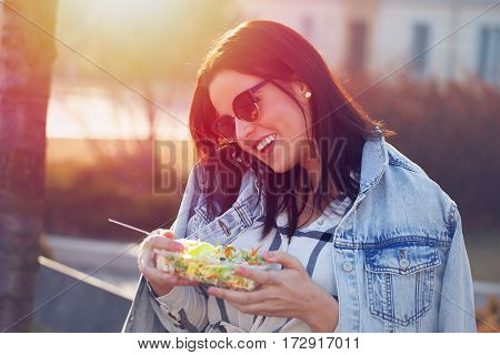 Young woman calling with salad in hands no time to eat