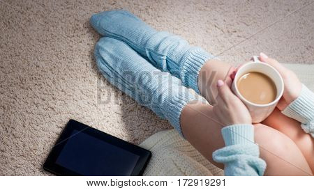 Young Woman Sitting On The Floor And Use The Tablet. Cozy Home Atmosphere. Feet Dressed In Cozy Knit