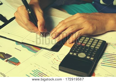 Woman Hands Writing Note About Expenses And Paperwork On Desk.