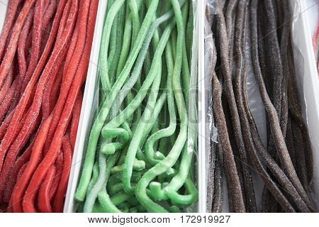 Various multi colored confectionery in the candy shop. Colorful tasty licorice candies for sale on retail market candy shop