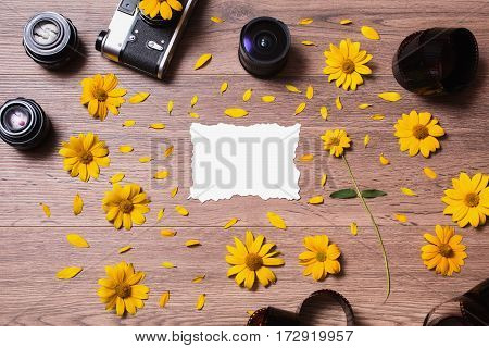 Old vintage camera lying on the wooden background. Film and three lenses lie on a table. Place for design. Blank white sheet of paper. Yellow flowers and petals. A flower with a green stem. Black camera. Lenses for camera