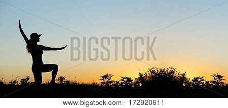 Silhouette website banner of a happy female as raising her arms at sunset