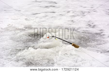 hole in the ice a short fishing rod fishing tackle white snow winter