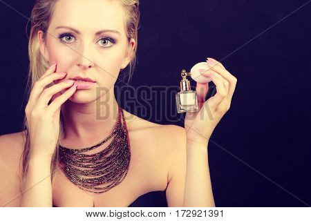 Smell elegance concept. Beautiful elegant blonde woman with necklace holding perfume bottle studio shot on dark background