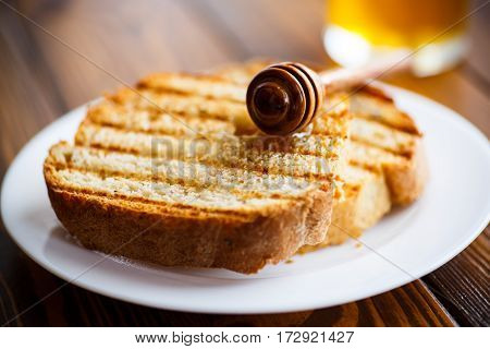 Fried toast with honey on a wooden table