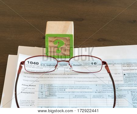 Question mark wooden block illustrating problems or issues in completing US IRS tax form