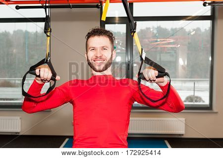 Handsam man exercising her muscles with help of suspension trainer sling or suspension straps isolated on white background.