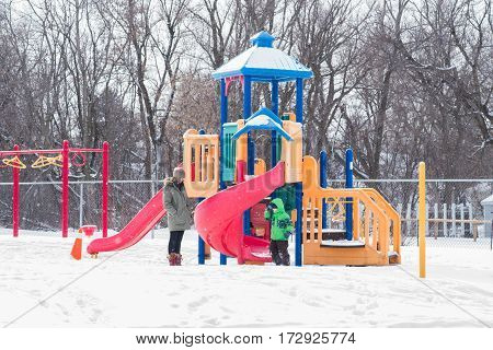 Playground in Canada with mother and child while snowing