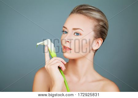Spa Woman with White Lily Flower on Blue. Healthy Model with Clear Skin Aesthetic Medicine and Treatment Background