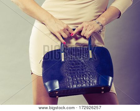 Clothing and accessories. Fashionable woman wearing dress and holding black elegant bag. Part body of mid aged lady on gray.