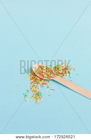 Easter decoration wooden spoon with colored sugar ingredients on a light blue background minimal design with space for text vertical image