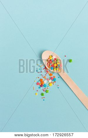 Easter decoration wooden spoon with colored sugar ingredients on a light blue background minimal design vertical image