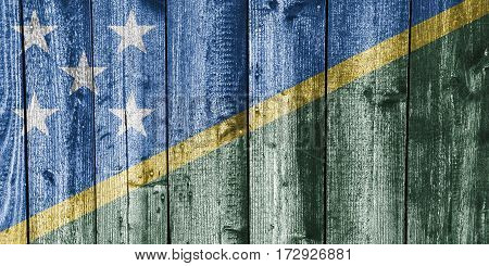 Colorful and crisp image of flag of the Solomon Islands on weathered wood