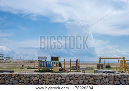 Massive clouds above the sea with the playground on the seashore of Calafell, Barcelona, Catalonia, Spain