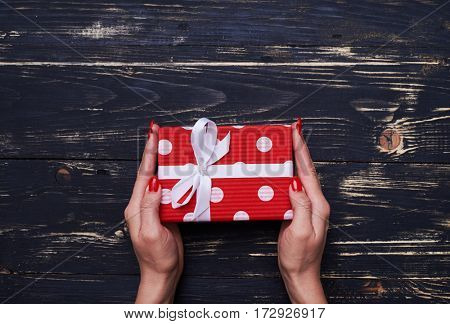 High angle of little dotted gift box keeping by female hands. Female hands with perfect red manicure holding present box over shabby wooden background