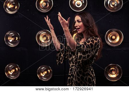 Side view of seductive young woman in a sexy leopard dress raised her hands up isolated over spotlights. Exhilarated young female singer