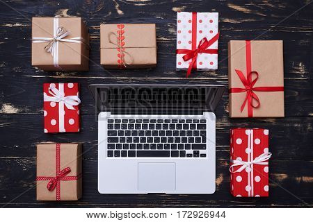 High angle of silver laptop encircled with many gift boxes isolated over gunge wooden flat lay background