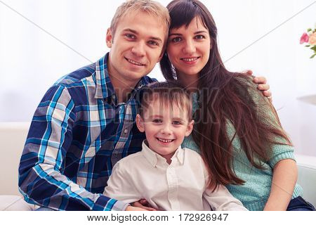 Close-up of young adorable family with kid at home. Sitting on the sofa in the living room. Enjoying time together. The concept of family harmony
