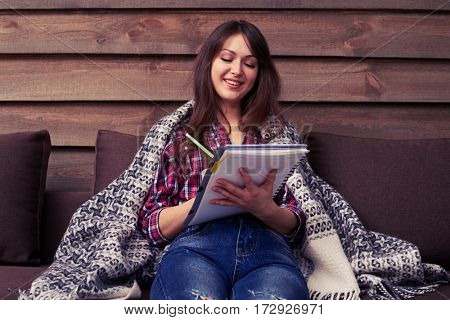 Mid shot of young woman on the sofa. She is thinking, planning and writing down notes. Feeling comfortable and relaxed