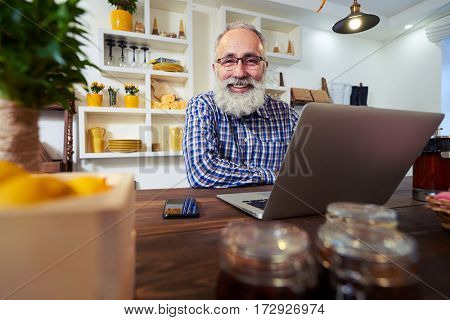 Low angle shot of joyful and laughing softly bearded man. Man looking at the camera while working on the computer. Sitting in a kitchen. Enjoying