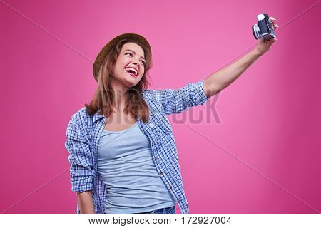 Mid shot of exhilarated woman smiling while making selfie photo. Wearing checked shirt and straw hat