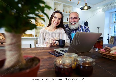 Side low angle shot of senior man sitting near affectionate woman as they are working on the laptop in the kitchen. Couple working at computer
