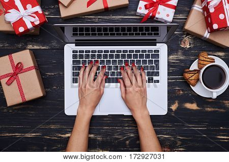 Top view of slim hands of woman typing on the silver laptop surrounded with gift boxes. Festive mood, valentine day