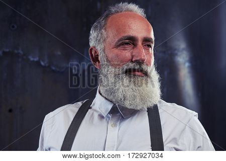 Low angle portrait of good-looking mature man with gray bearded over background with light. Man wearing white shirt and suspenders looking sideways